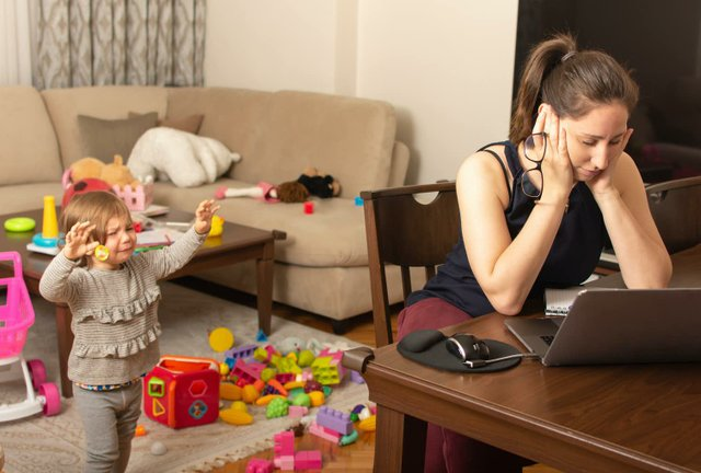 Mother hunched over laptop, with small child crying.