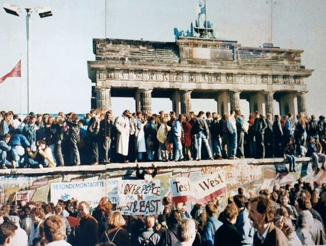 Crowds stand atop the Berlin Wall