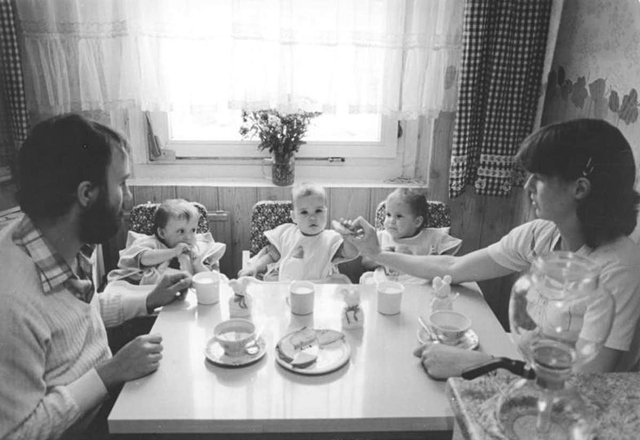 A black and white picture of a couple and three children.