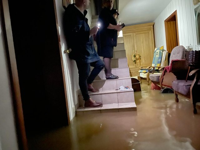 Two people stand on a staircase beset by rising water.