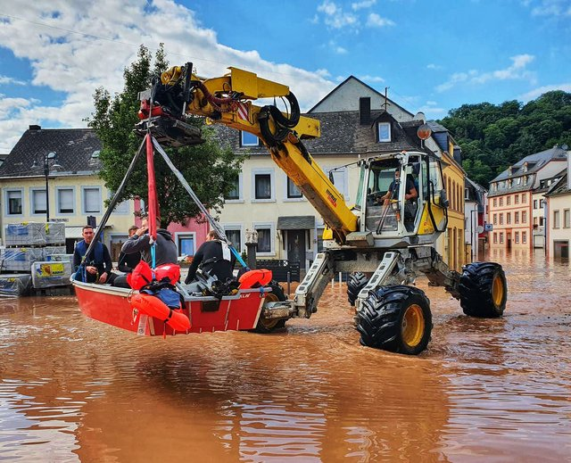 A digger left up a boat containing people in a flooded town